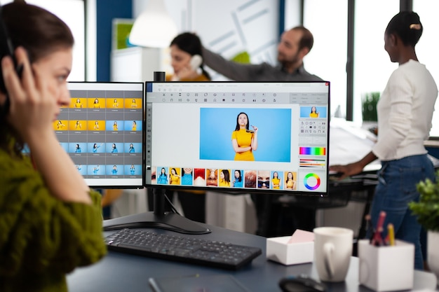 Retoucher woman working on computer with two monitors and stylus pencil