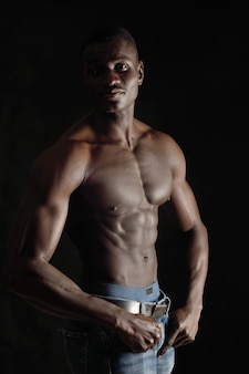 Retrato de un hombre sin camisa sobre fondo negro