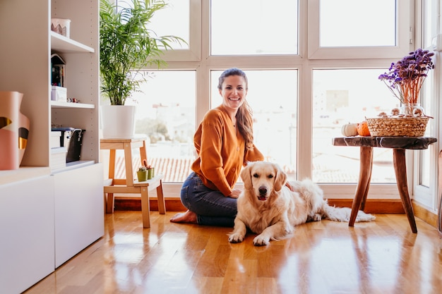 Красивая женщина обнимая ее прелестную собаку золотого retriever дома. любовь к животным концепции. образ жизни в помещении