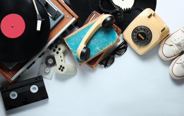 Ретро 80-х объектов поп-культуры на белом фоне. копировать пространство кроссовки, поворотный телефон, виниловый проигрыватель, старые книги, аудио, видеокассеты, 3d очки, геймпад.