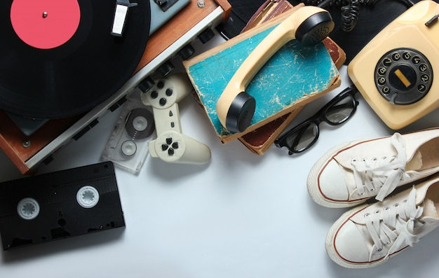 Retro 80s pop culture objects on white background. copy space. sneakers, rotary phone, vinyl player, old books, audio, video tapes, 3d glasses, gamepad.