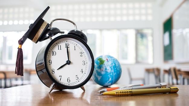 Retro alarm clock 2 o'clock, left side on table teacher with earth global map