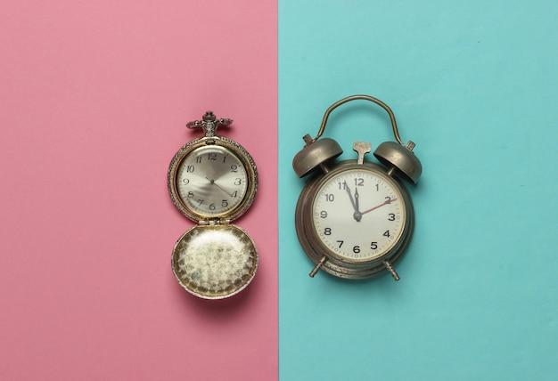 핑크 블루 파스텔 배경에 레트로 알람 시계와 포켓 시계. 오전 11:55 새해.