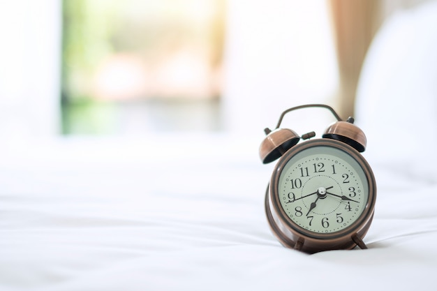 Retro alarm clock on bed in the morning sunlight, wake up, fresh relax, have a nice day and daily routine concept