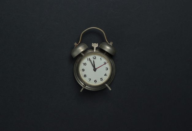 Retro alarm clock on black background. 11:55 am. new year. top view