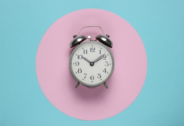 Retro alarm clock on blue background with pink pastel circle. top view