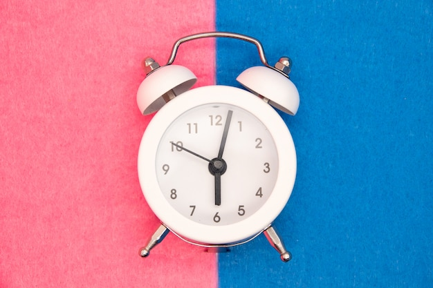 Retro alarm clock on the blue and pink background