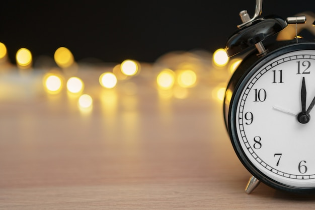 Retro alarm clock on blurred christmas background with bokeh