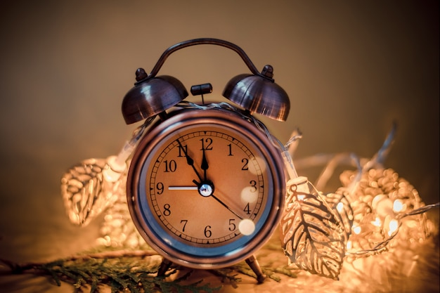 Retro alarm clock on blurred christmas decoration