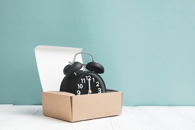 Retro alarm clock in brown delivery cardboard box or tray on white wood