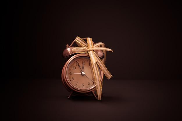 Retro alarm clock in golden bow on black