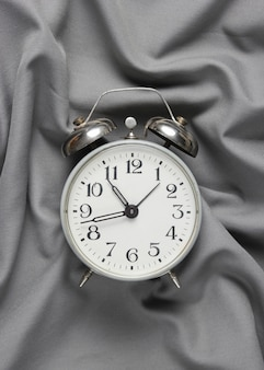 Retro alarm clock on a gray silk bedspread.