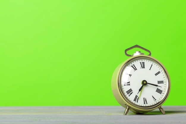 Retro alarm clock on green wall background