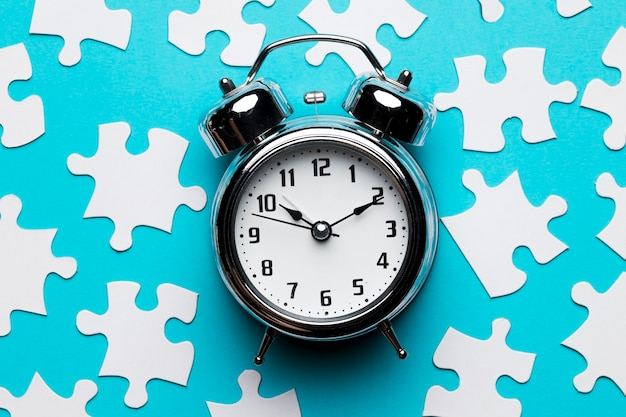 Retro alarm clock and jigsaw puzzle pieces on blue backdrop