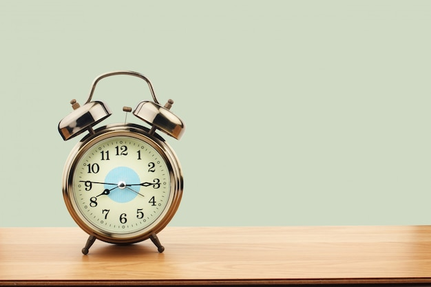 Retro alarm clock on old wooden table on green wall background