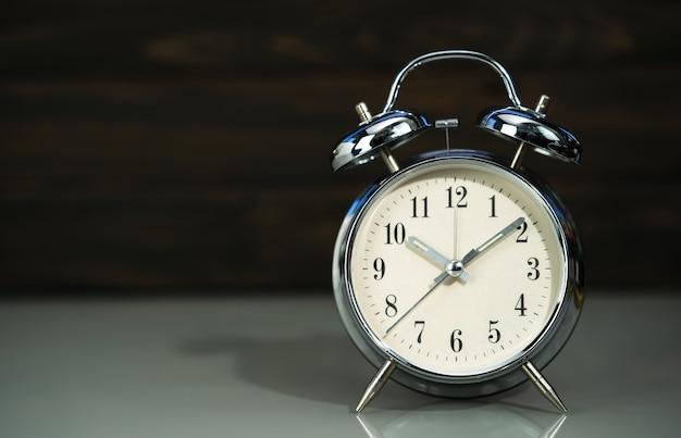 木の背景の近くのテーブルのレトロな目覚まし時計