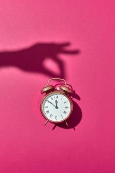 Ретро-будильник окрашен в золотой цвет с жесткими тенями от руки женщины, держащей его на ярко-розовом фоне, копией пространства.