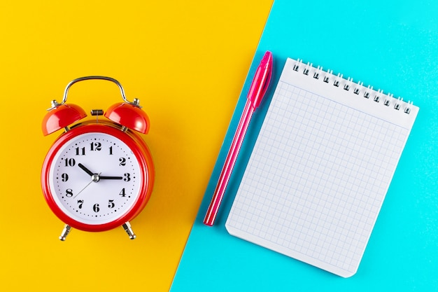 Retro alarm clock next to a pen and notebook on a blue and yellow background