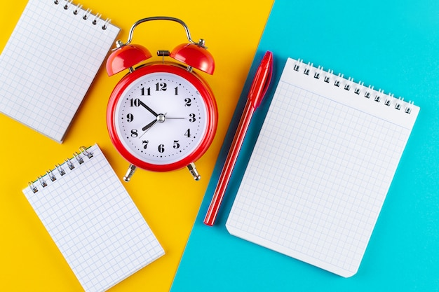 Retro alarm clock next to a pen and notebook on a blue and yellow background.