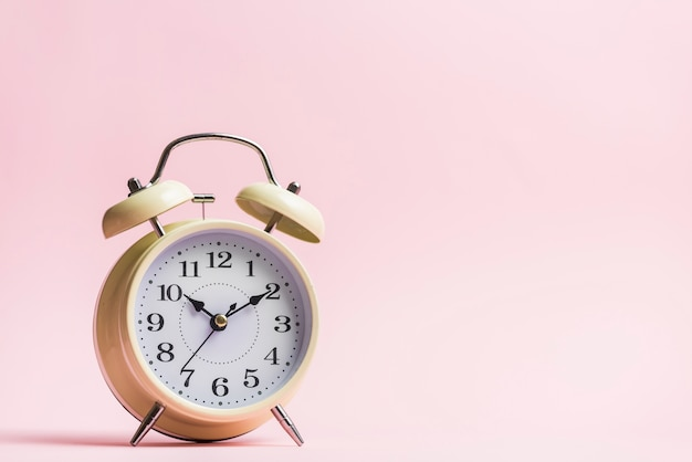 Retro alarm clock on the pink background