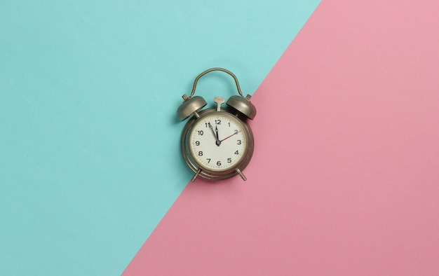 Retro alarm clock on pink blue pastel  background. 11:55 am. new year. top view