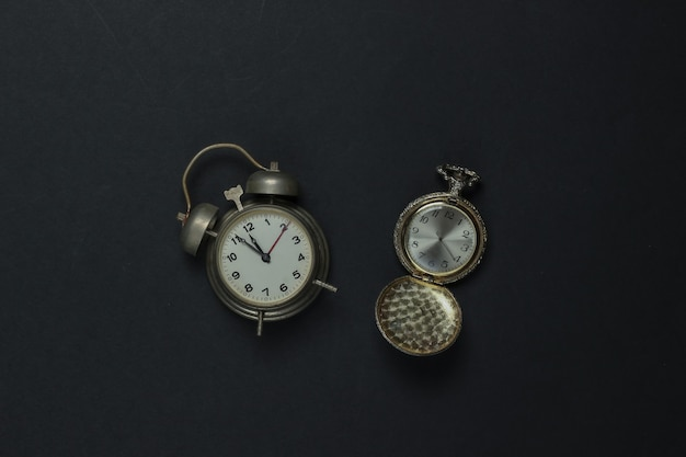 Retro alarm clock and pocket watch on black background. 11:55 am. new year.