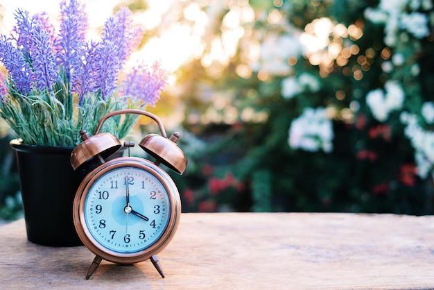 레트로 알람 시계는 아름 다운 라벤더 나무 테이블에 넣어.