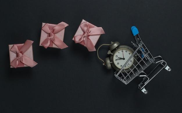 레트로 알람 시계, 쇼핑 트롤리, 검은 바탕에 활과 선물 상자. 오전 11:55 새 해, 크리스마스 개념입니다. 휴일 쇼핑. 평면도