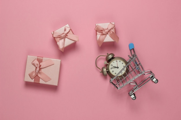 레트로 알람 시계, 쇼핑 트롤리, 핑크 파스텔 배경에 활과 선물 상자. 오전 11:55 새 해, 크리스마스 개념입니다. 휴일 쇼핑. 평면도