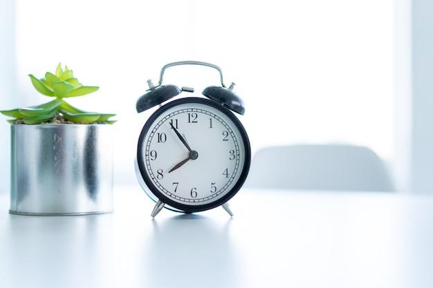 Ретро будильник, стоящий на белом столе, чистый домашний фон, концепция утреннего времени