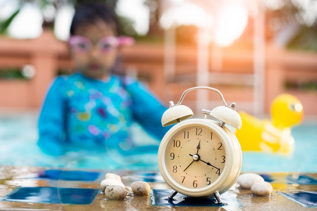 Retro alarm clock  at the swimming pool with children wearing swim goggles.
