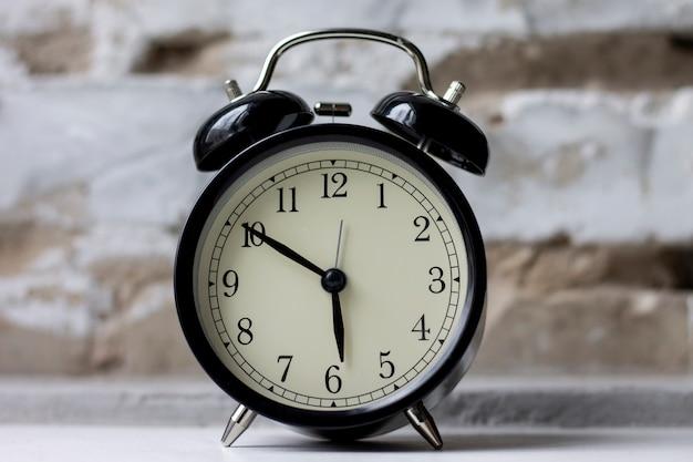 Retro alarm clock on table on brick wall background