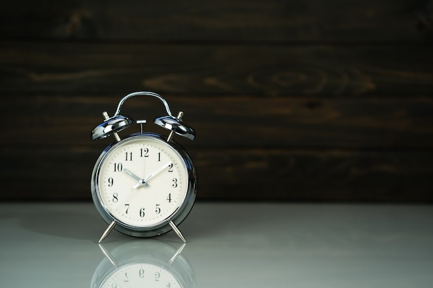 Retro alarm clock on table near wood background