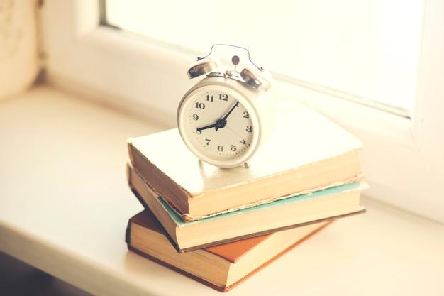 Retro alarm clock with books on the window