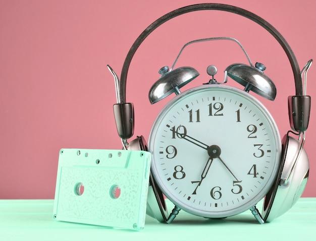 Ретро будильник с наушниками и аудиокассеты на деревянный стол