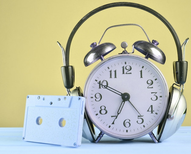 Retro alarm clock with headphones and audio cassette on wooden table on pastel background