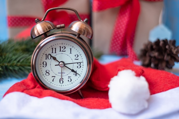 Retro alarm clock with merry christmas gift box or present and santa claus hat