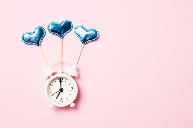 ピンクの背景のパーティーの装飾とレトロな目覚まし時計