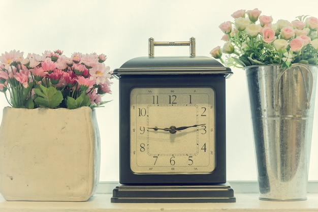 Retro alarm clock with a vase of flowers in the interior