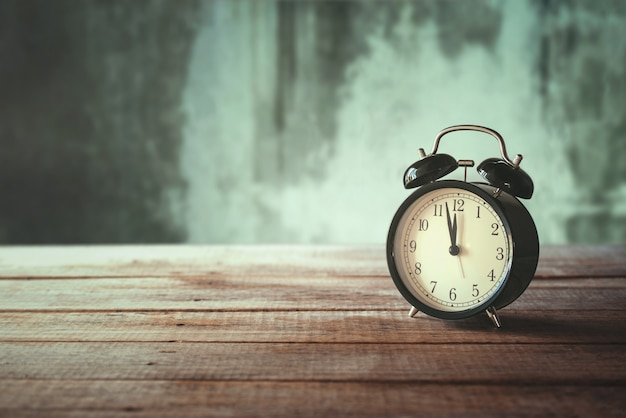 Retro alarm clock on wood table with grunge background time for lunch concept.