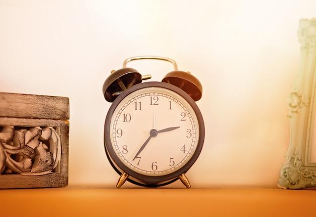 Retro alarm clock on wooden ton the shelf, vintage style.