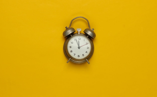 Retro alarm clock on yellow background. 11:55 am. new year. top view