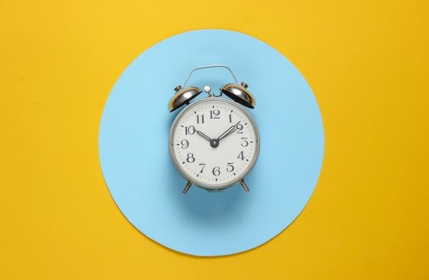 Retro alarm clock on yellow background with blue pastel circle.
