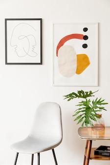 灰色の椅子、テーブル、ランプ、本立て、毛布、白い壁にポスターフレームギャラリーを備えたリビングルームのレトロでヴィンテージなインテリア