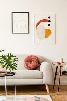 灰色のソファ、テーブル、ランプ、本立て、毛布、白い壁にポスターフレームギャラリーを備えたリビングルームのレトロでヴィンテージなインテリア