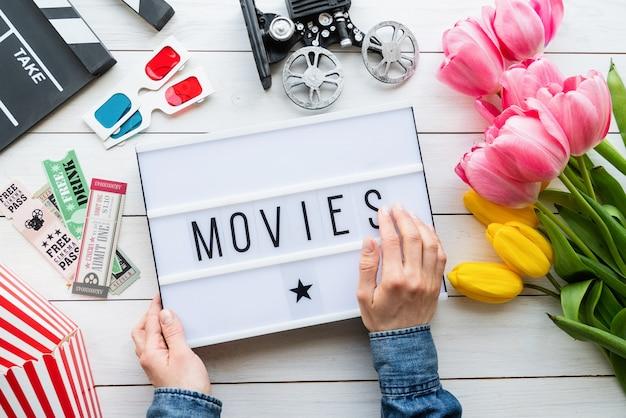 レトロとヴィンテージ。単語の映画、カチンコ、チケット、チューリップ、3dメガネとライトボックスを保持している女性の手の上面図