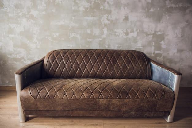 Ретро античный диван на фоне старой штукатурки