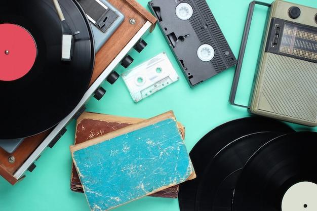 Ретро атрибуты, медиа 80-х. виниловый проигрыватель, видеокассеты, аудиокассеты, записи, радио, старые книги на синем фоне. вид сверху