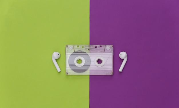 紫緑色の背景にレトロなオーディオカセットとワイヤレスイヤホン。