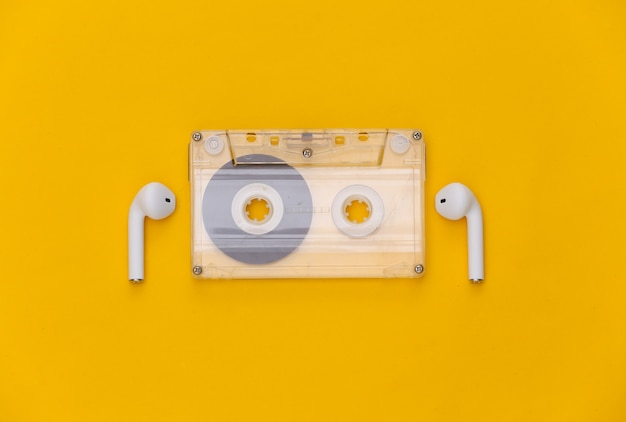 黄色の背景にレトロなオーディオカセットとワイヤレスイヤホン。